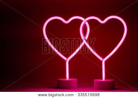 Two glowing pink neon hearts Valentines day party concept