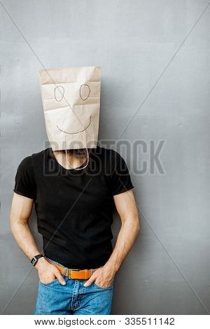 Portrait Of A Man With Paper Bag On His Head Standing On The Grey Background. Concept Of Facelessnes