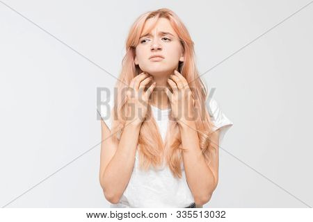 Portrait Of Young Woman In White T-shirt Who Scratching Itchy Neck Both Hands. Itching Causes The Gi