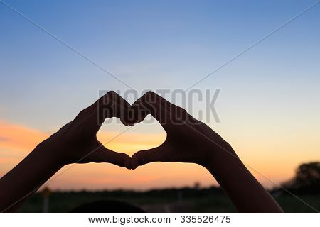 Female Hands In The Form Of Heart Against Sunlight In Sunset Sky, Love Concept, Hands In Shape Of Lo