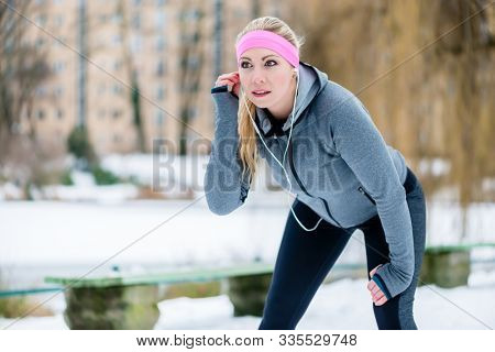 Fit woman listening to music while having break from running sport in winter