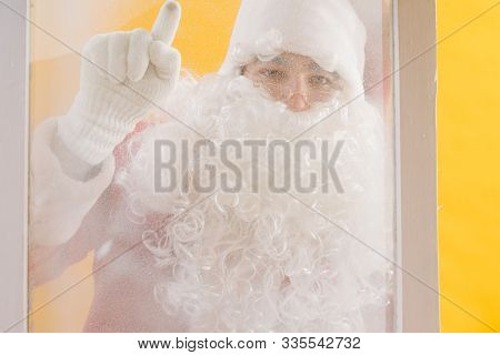Santa Claus Is Knocking At The Frozen Window With Index Finger. View From Home.