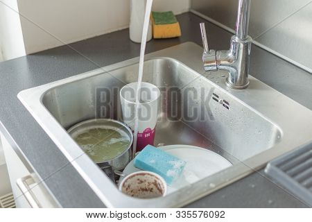 Unwashed Dishes And Utensils In A Kitchen Sink. Pile Of Dirty Dishes In A Sink. Washing Dishes Conce