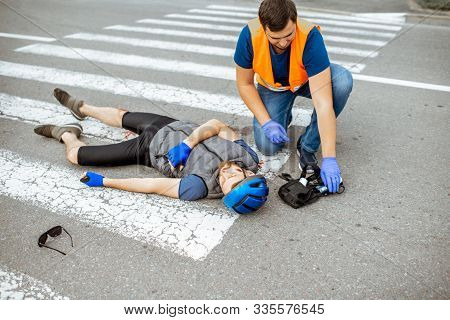 Road Accident With Injured Cyclist On The Pedestrian Crossing With Passerby Pedestrian Providing Fir