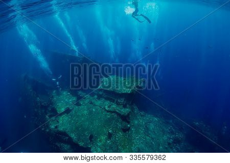 Freediver Glides Underwater At Shipwreck In Tulamben, Bali. Freediving In Ocean