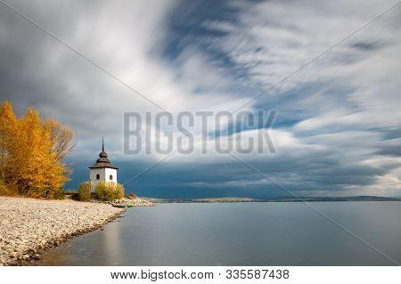 Church Tower Of Virgin Mary At The Shore Of The Liptovska Mara Dam In The Morning Light At Autumn, T