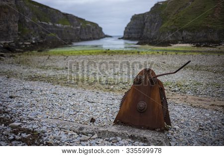 A Rusty, Abandoned Piece Of Machiney That Has Gears, Rests On A Rocky Beach At Geodha Smoo At Smoo C
