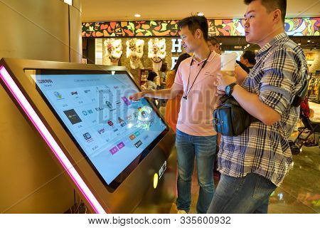 SHENZHEN, CHINA - CIRCA NOVEMBER, 2019: a man use interactive touch kiosk at Wongtee Plaza shopping mall in Shenzhen