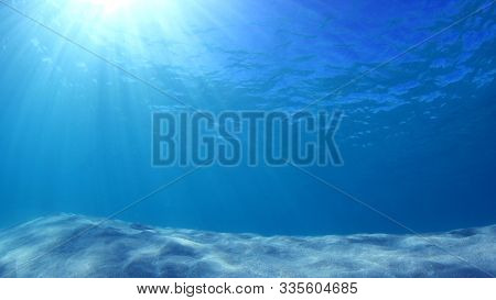 Underwater photo of blue ocean, sunbeams and sandy sea floor