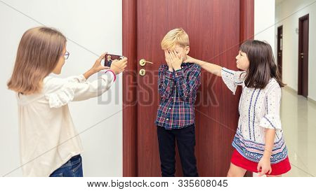 Bullying At School With Two Girls Making Fun Of Little Boy Taking Pictures While Being Bullied - Kid