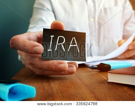 Man Holds Individual Retirement Account Ira Sign On The Black Sheet.