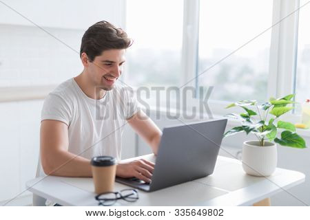 Portrait Of A Smiling Man Using Laptop In The Kitchen At Home