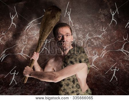 A Man In Glasses And In Primitive Skin With A Cudgel In His Hands Threatens. The Metaphor Of Politic