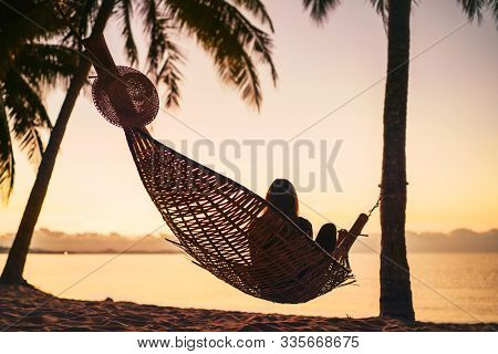 Young Woman Relaxing In Hammock Hinged Between Palm Trees On The Sand Beach At Orange Sunrise Mornin