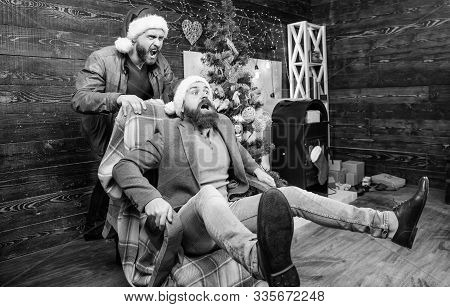 Man Push Armchair With Friend. Cheerful Men Having Fun At Home. Christmas Fun. You Will Never Be Bor