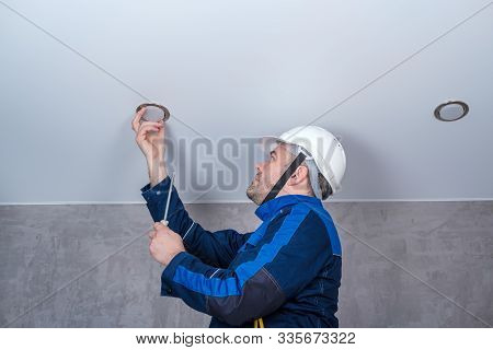 A Man Electrician In Uniform And Helmet Changes Repairs The Ceiling Lamp