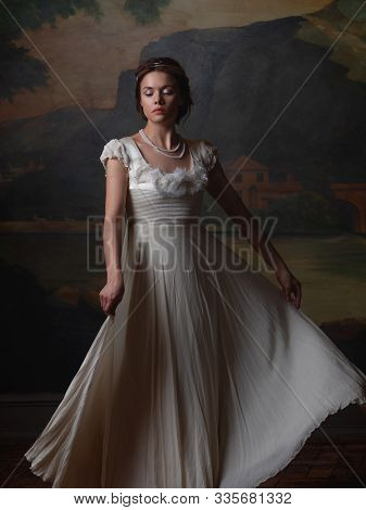 Beautiful Young Woman In A White Long Dress In The Style Of The 19th Century. Portrait In The Style