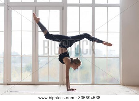 Young Sporty Flexible Woman Practicing Yoga, Doing Handstand Pose With Splitted Legs, Indoor Full Le