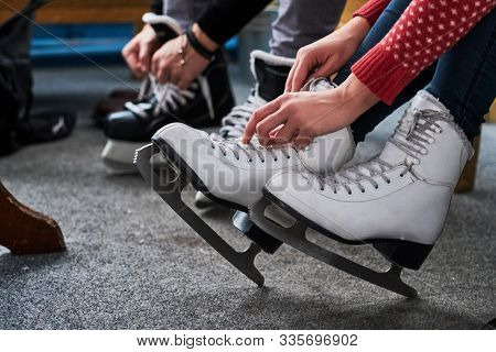 Young Couple Preparing To A Skating. Close-up Photo Of Their Hands Tying Shoelaces Of Ice Hockey Ska