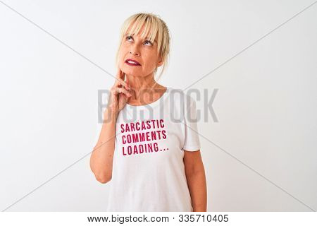 Middle age woman wearing fanny t-shirt with irony comments over isolated white background serious face thinking about question, very confused idea