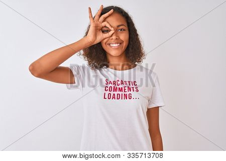 Brazilian woman wearing fanny t-shirt with irony comments over isolated white background with happy face smiling doing ok sign with hand on eye looking through fingers
