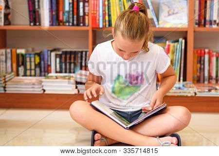 Teenager Girl In Library In Front Of Books. Cute Young Child Sitting On Floor And Reading Book. Litt