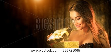 Surprised Christmas Winter Woman opening magic Christmas Gift box and smiling. Fairy tale. Beautiful New Year and Xmas scene, Beauty Fashion Model Girl With Present Box at night. Holiday Magic