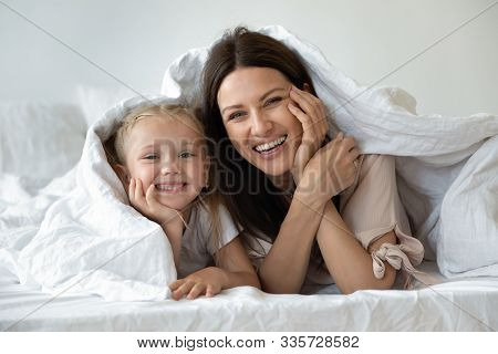 Happy Family Looking At Camera Covered With Warm White Duvet