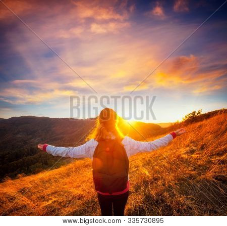 Carefree hipster girl enjoying nature on top of mountain with sunset. Image of freedom concept. Hiker during travel holidays vacation outdoors. Photo toned style instagram filters, vintage effect.