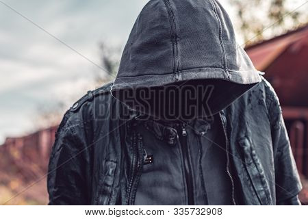 Faceless hooded homeless man among old obsolete freight train wagons, conceptual portrait, selective focus poster