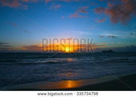 In Images Rising Sun On The Horizon Above A Calm Ocean Or Sea. On The Blue Sky White Clouds