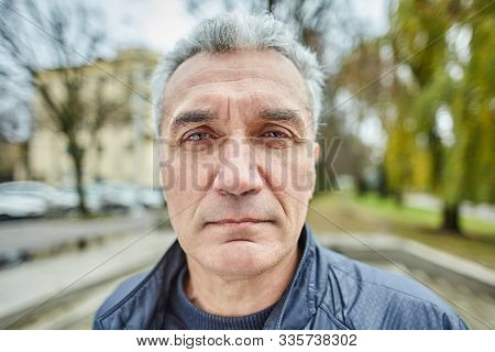 Aged Serious Man Is Standing Outdoors. Portrait Of Mature Sad Businessman About 56 Years Old On The