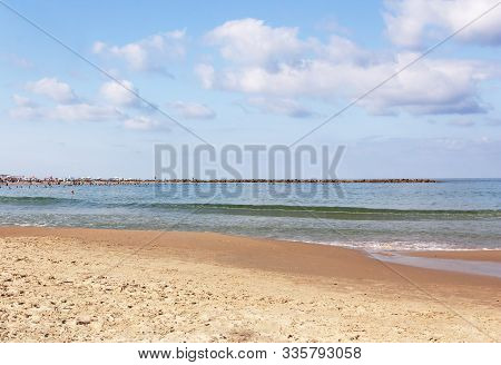 View Of The City Beach With A Breakwater On The Horizon