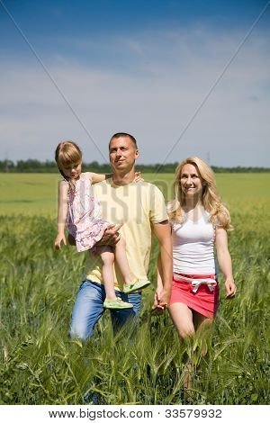 Young Family Running Across The Field