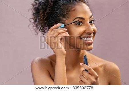 African woman applying black mascara on eyelashes with brush. Young beautiful woman applying makeup on eyes. Portrait of black beauty girl applying makeup isolated over pink background with copy space