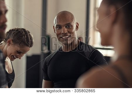 Friends talking and laughing together in gym. Group of four multiethnic people relaxing in conversation. Black sweaty guy and young women talking to each other while resting after intensive training.