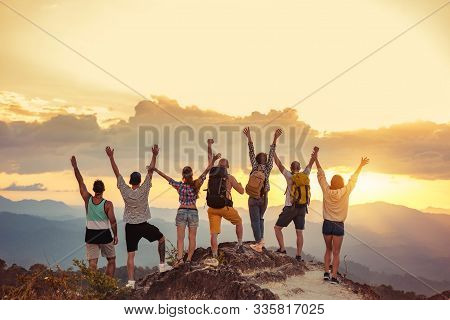 Group Of Happy Friends Stands With Raised Arms At Sunset Mountain And Enjoys Sunset