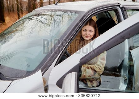 Beautiful Young Sexy Woman In Car Looking From Window And Autumn Forest Ackground