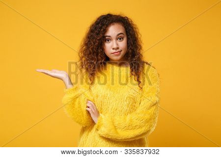 Perplexed confused young african american girl in fur sweater posing isolated on yellow orange background in studio. People sincere emotions lifestyle concept. Mock up copy space. Pointing hand aside. poster