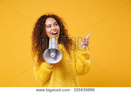 Cheerful Young African American Girl In Fur Sweater Posing Isolated On Yellow Orange Wall Background