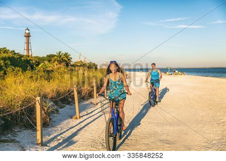 Biking couple cycling on florida beach tourists riding bikes in Sanibel island, Gulf of Mexico. People having fun summer lifestyle in sun. Asian girl laughing on recreational bike, man bicycling.