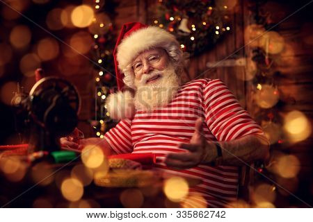 Santa Claus is preparing for Christmas at his wooden home - he sews gifts on a sewing machine. Santa Claus workshop. Christmas decoration.
