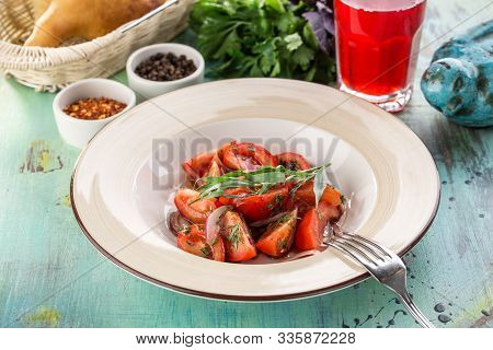 Healthy Appetizer Fresh Tomato Salad In White Bowl With Red Onion And Estragon On Blue Wooden Table
