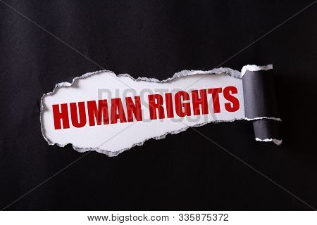 Top View Of Black Torn Paper And The Red Text Human Rights On A White Background. Human Rights Conce