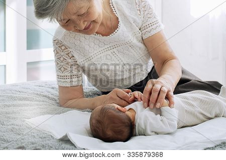 Grandmother Admires Her Sweet Granddaughter. Great-grandmother Plays With A Newborn Great-granddaugh