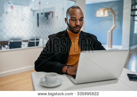 Focused Black African American Millennial Man Sitting At Desk Using Laptop And Earpods In Coworking