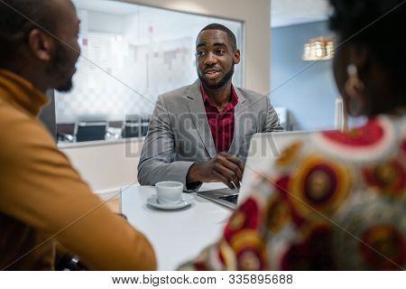 African Couple Meeting With Black Male Financial Advisor Bank Manager Relationship Counsellor In Off