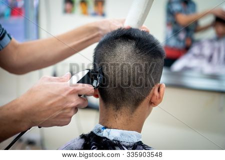 An Asian Boy In The Barbershop  ,boy Getting Haircut By Barber In Barbershop