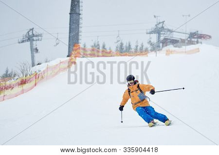 Proficient Young Skier Skiing Downhill From High Snow-covered Slope With Net On Edge. Winter Sports