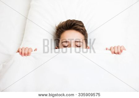 Handsome sleeping child boy lying bed hiding and covering face with blanket